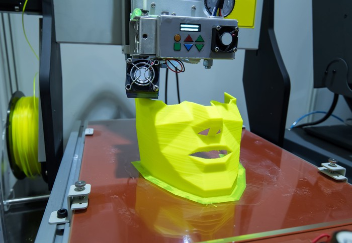 A 3D printer printing a human face or mask from yellow plastic.