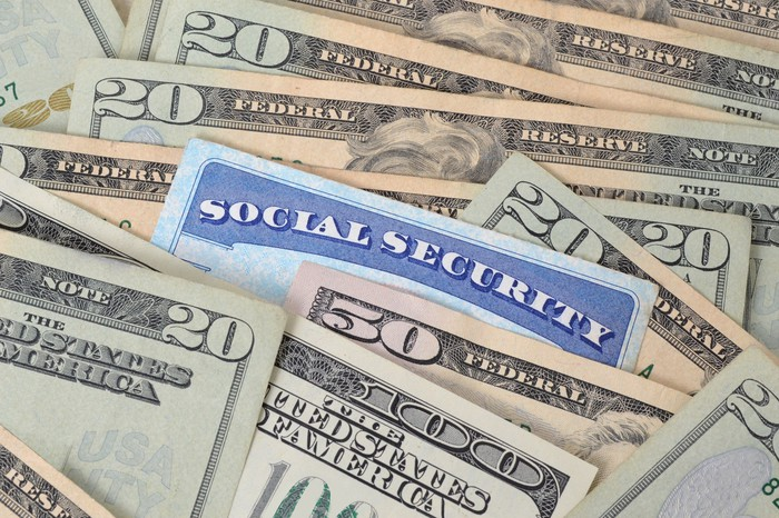 Blue Social Security card sticking out of a pile of U.S. currency.