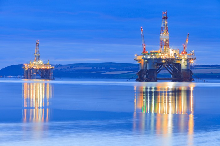 Two offshore drilling rigs on the water at dusk.