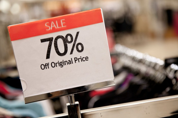A sale sign for 70% off the original price of some clothes