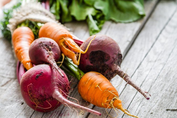 Carrots and beets in a bunch on wood planks.