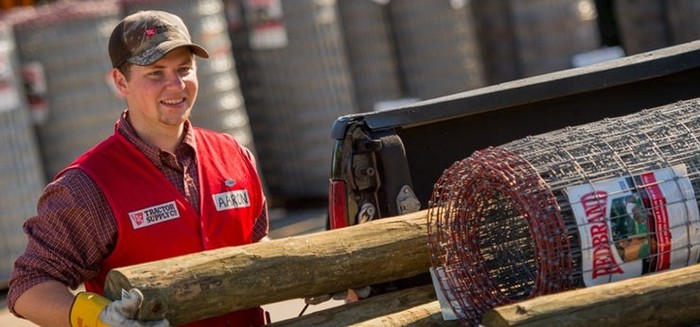 Tractor Supply Company employee smiling and moving fencing materials.