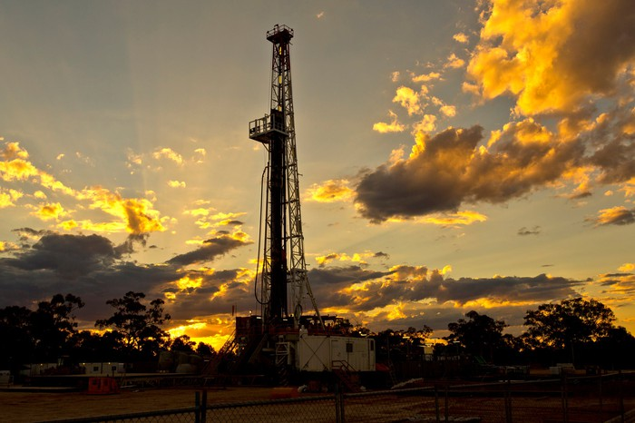 A drilling rig with the sun peeking through the clouds behind it.