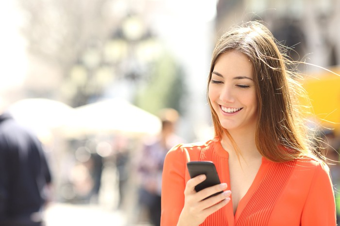 A woman smiles as she looks at her smartphone
