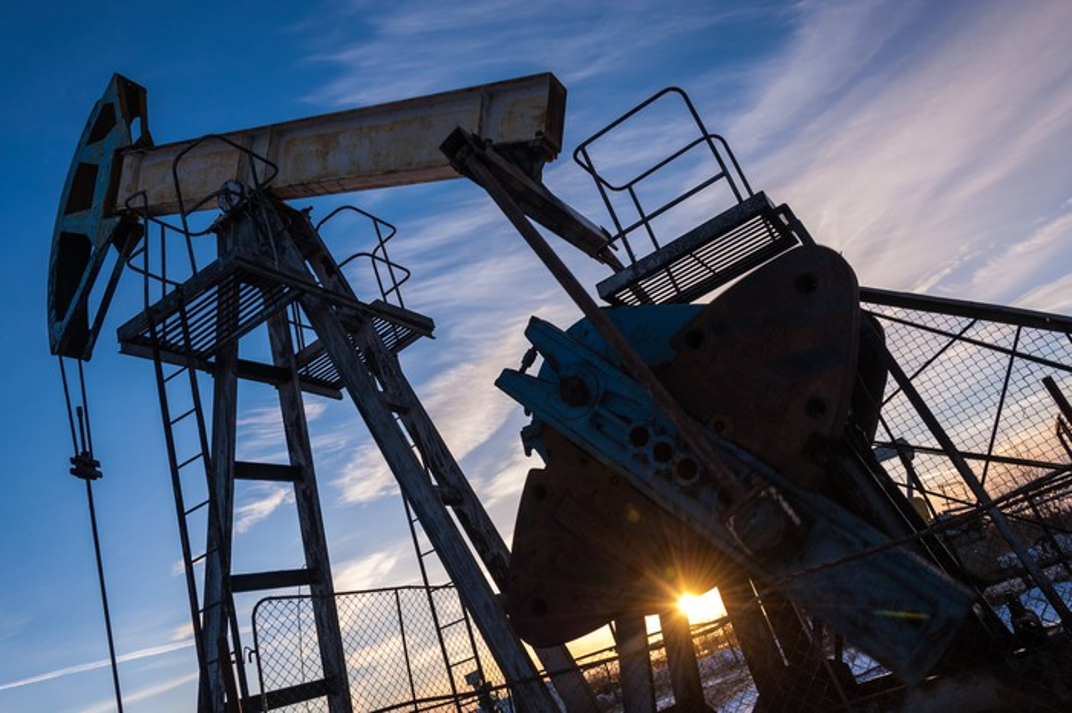 An oil pump with the sun shining through.