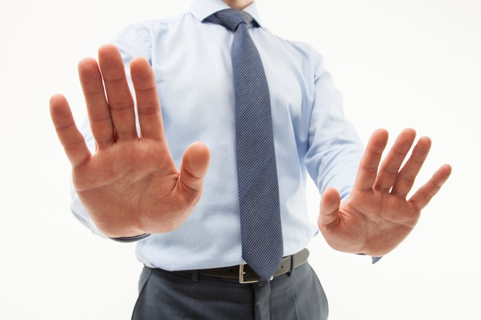 Businessman signaling rejection with raised palms.