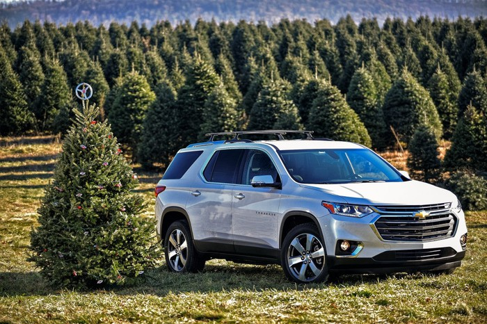 Chevrolet's Traverse parked next to a Christmas tree.