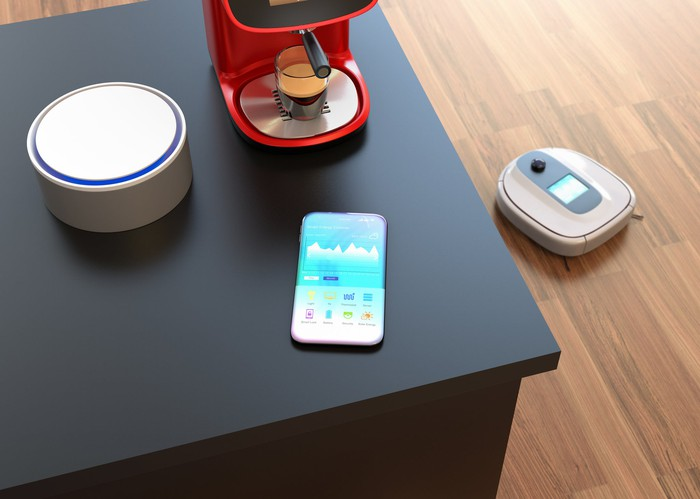 A smart home with a connected speaker, robotic vacuum, and smartphone