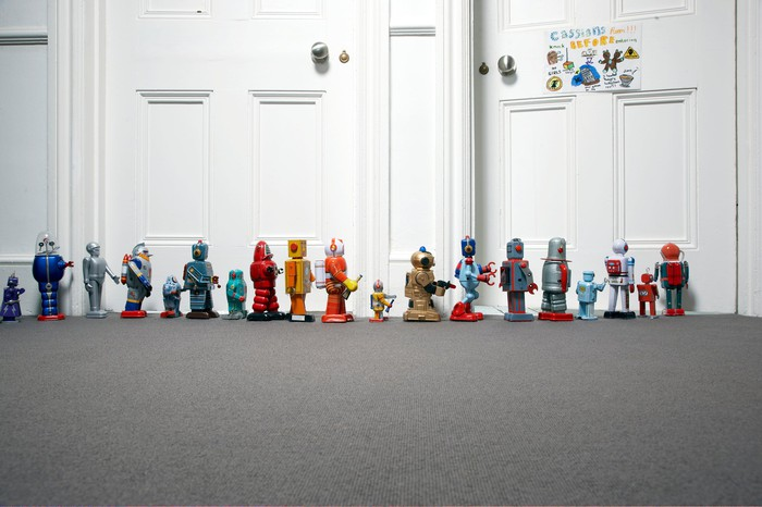 Toys lined up marching on a floor.