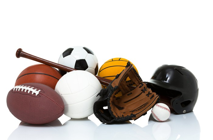 Sports equipment in a pile on the floor.