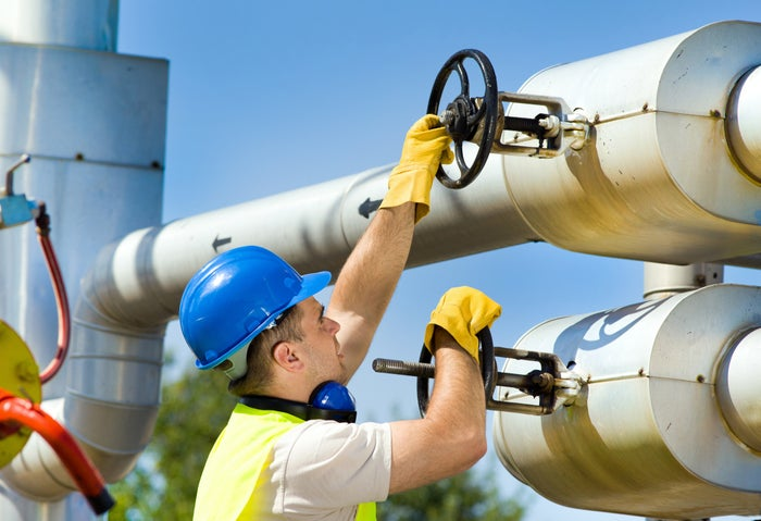 A man turning handles on a pipeline