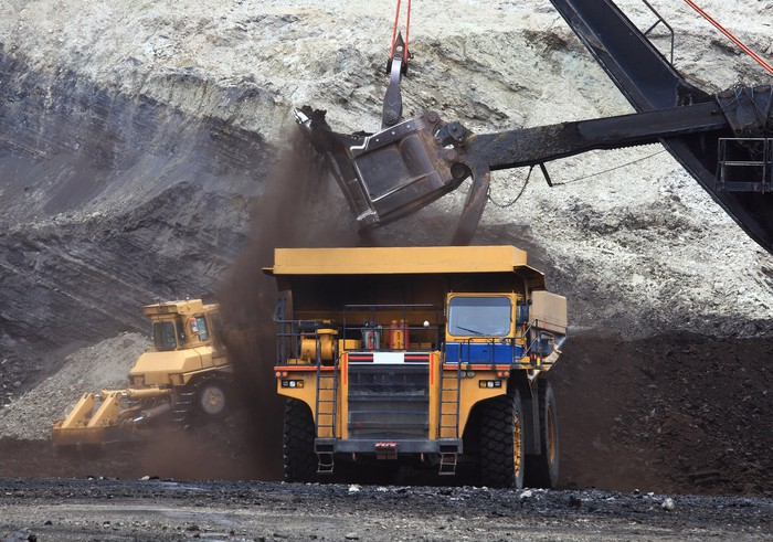 Large excavator filling up a dump truck in a mine.