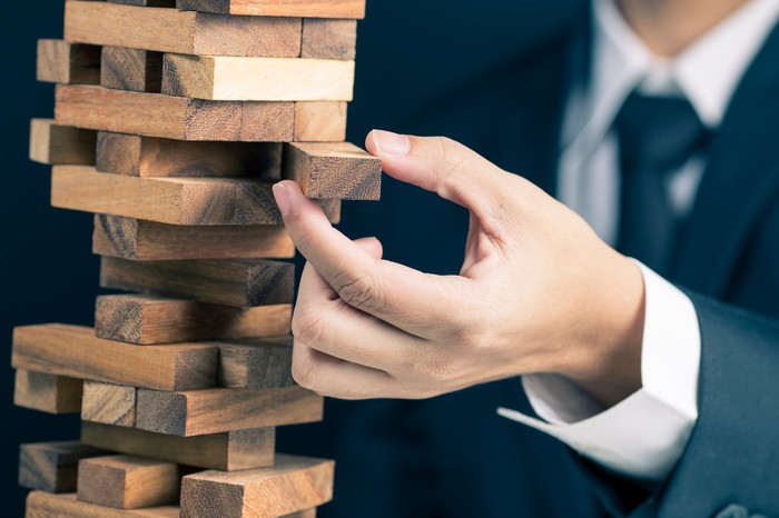 Picture of a business man precariously close to causing a large structure of wood blocks to come tumbling down.