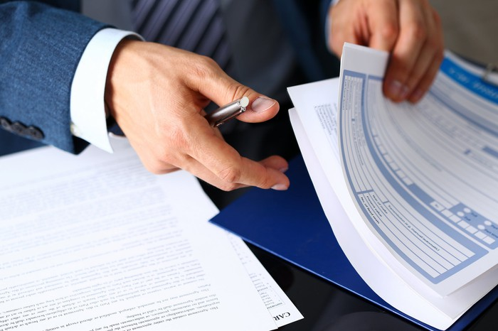 Man rifling through pages of contracts
