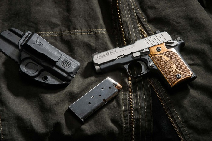 A Sig Sauer P938 and holster on top of a jacket.