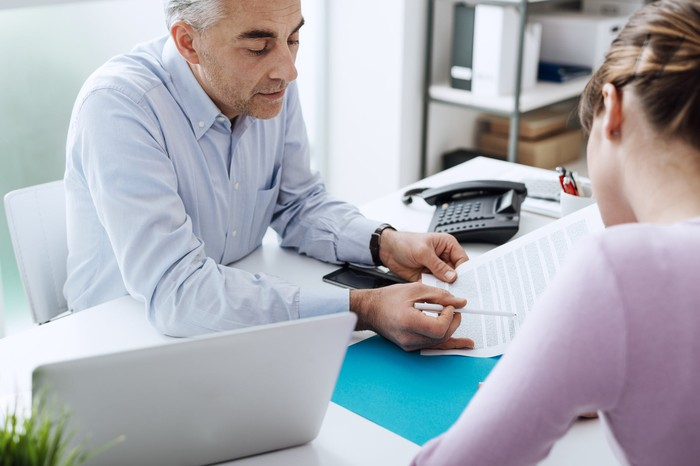 In an office setting, a man on one side of a desk reviews a document with a woman