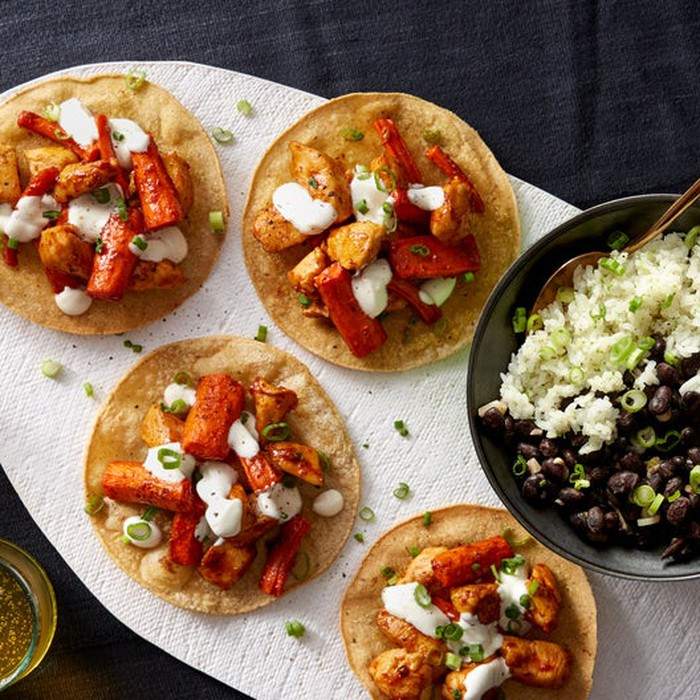 Several chicken tostadas shown on top of a large tortilla.