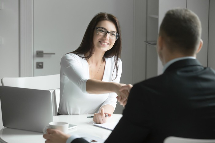 Woman extending her hand to man in suit