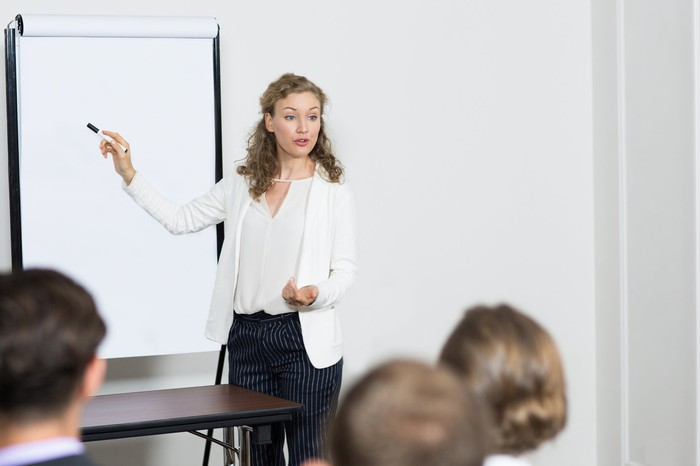Professionally dressed female pointing to a white board in front of others