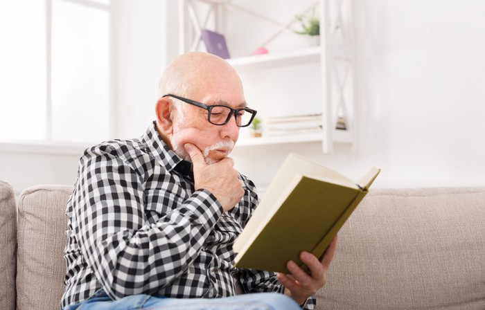 Senior man reading a book on a sofa, with a hand against his chin.