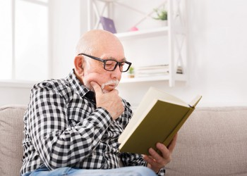 senior male reading a book_GettyImages-882987818
