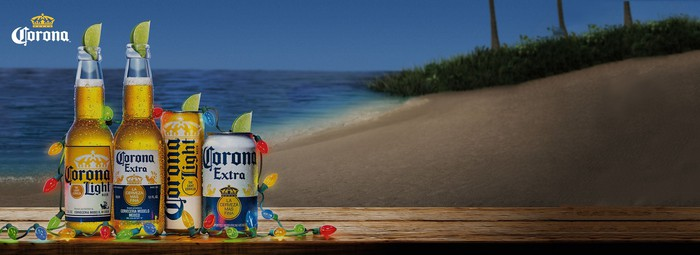 A row of Corona beverages decked with Christmas lights on the beach