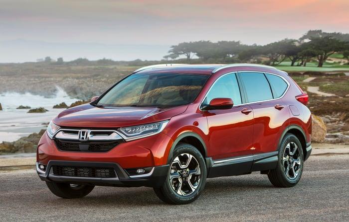 A red Honda CR-V crossover SUV parked near a beach.
