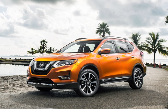 An orange Nissan Rogue crossover SUV parked on a sunny beach.