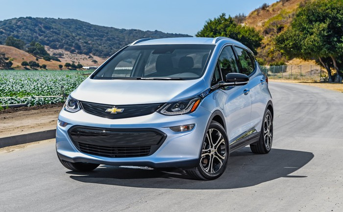A 2018 Chevrolet Bolt EV, a compact electric vehicle, on a sunny coastal road.