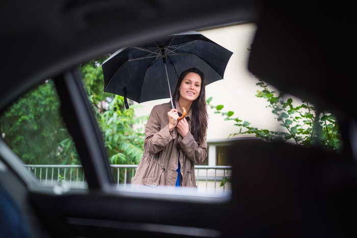 Woman holding a black umbrella peeks into a car window in front of her to check if it's her Uber ride