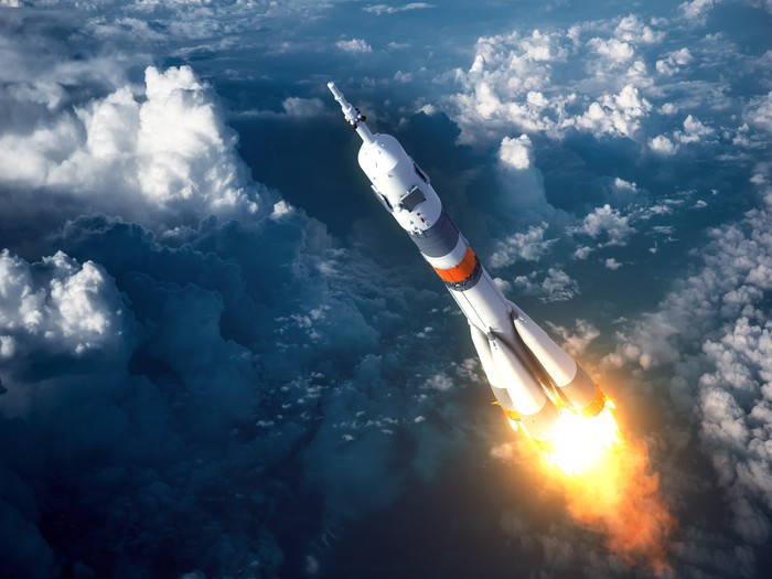A rocket ship soars from earth into space.