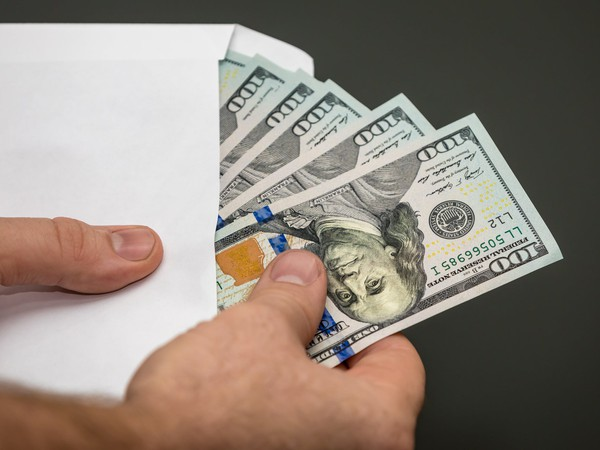 man holding an envelope with $100 bills_GettyImages-849671438