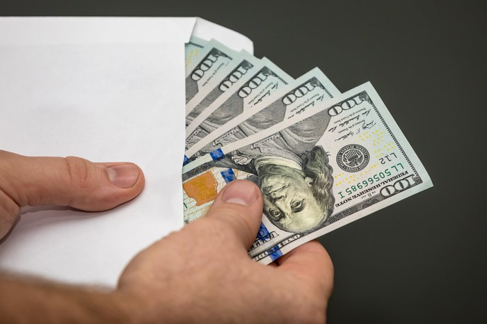 Man holding an open envelope with $100 bills