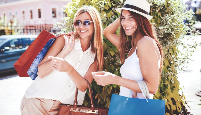 Two women holding shopping bags and smiling.