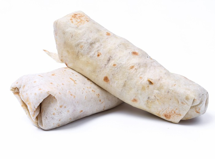 Two burritos on a table.