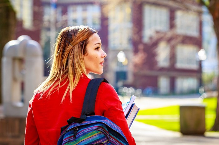 Woman wearing a backpack and holding textbooks.