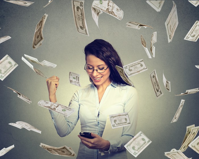 A woman checking her smartphone and pumping her fist as dollar bills fall around her.