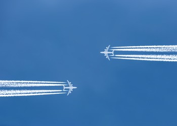 two planes flying toward each other jet trail
