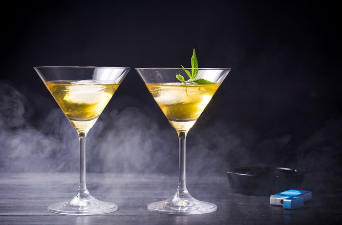 Two cocktail glasses with one containing a marijuana leaf
