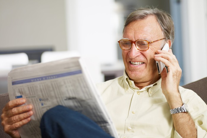 Older man squinting at a newspaper and talking on the phone