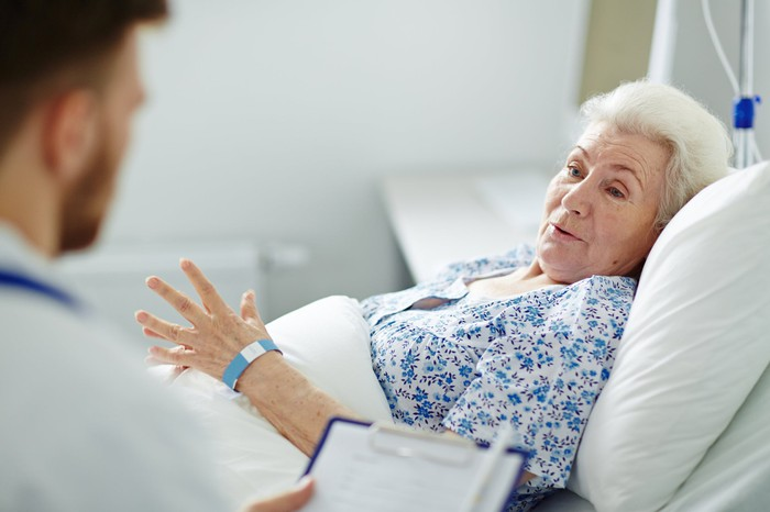 Senior woman lying in bed, talking to a doctor