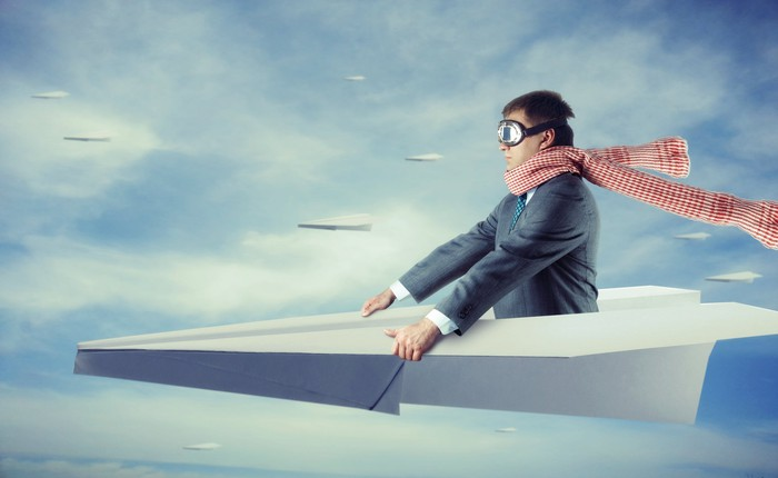 A man in a gray suit, goggles, and a long scarf rides a paper airplane in the sky