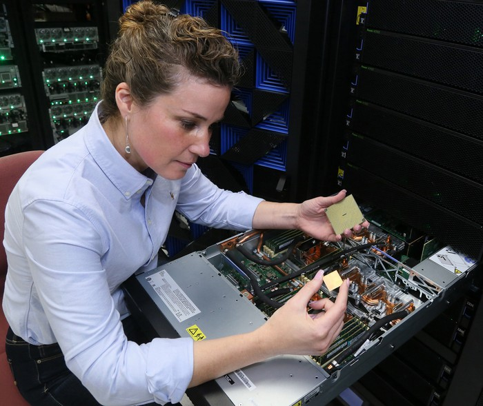 A woman holding an IBM POWER9 chip.
