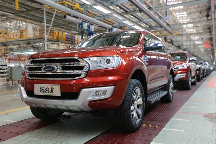 A line of Ford Everest SUVs at the end of a factory production line. The first Everest in line has a Chinese-language license plate.