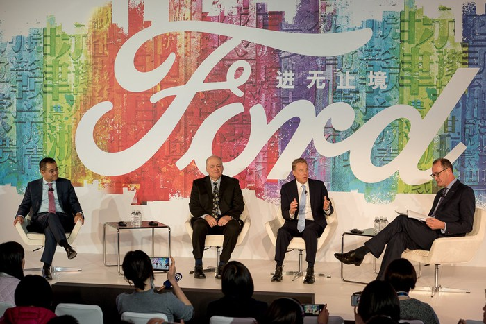 The four men are seated on a stage in front of a large rainbow-colored backdrop with a large Ford logo.