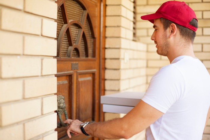 A pizza delivery man rings a doorbell.