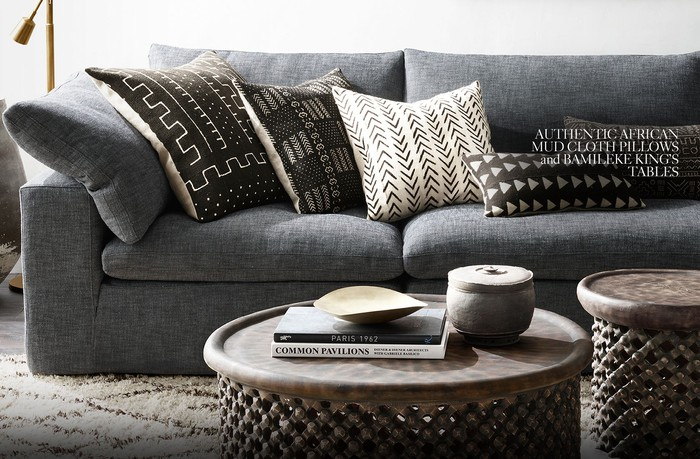 Gray couch with mud-colored pillows and decorative tables with a fuzzy rug and brass lamp.