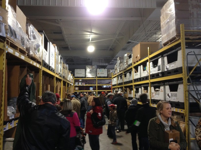 Aisle of warehouse store with pallets stacked to ceiling and dozens of customers shopping.