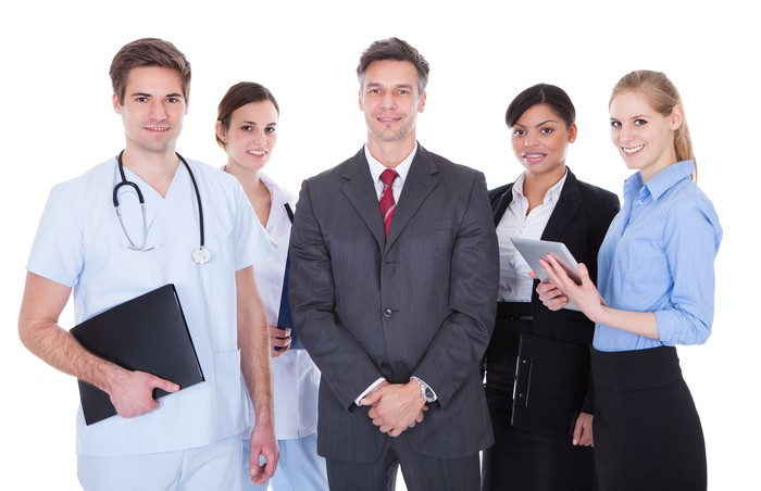 Business men and women standing next to healthcare professionals