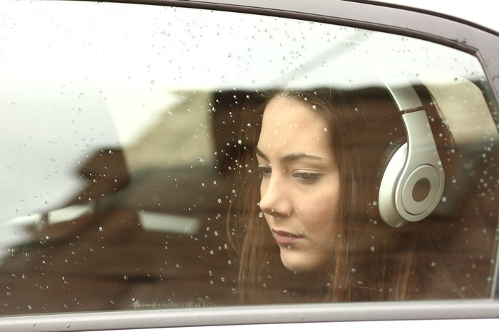 A sad woman wearing headphones, seen through a rain-washed car window.